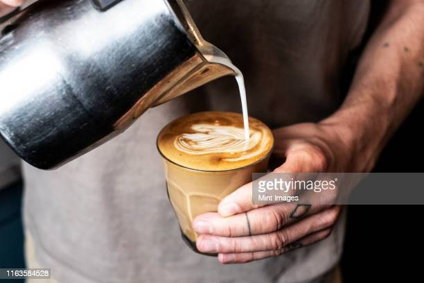 close up of person with tattooed finger pouring milk from metal jug into glass of cafe latte. - coffee stock pictures, royalty-free photos & images