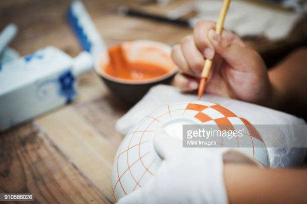 close up of person working in a japanese porcelain workshop, painting geometric pattern onto white bowls with paintbrush. - craft product stock pictures, royalty-free photos & images