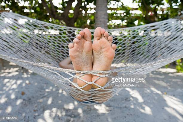 close up of person?s feet lying in hammock - woman soles stock photos and pictures