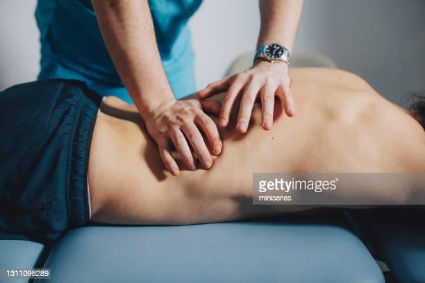 sluit omhoog van fysiotherapeut die lage rug masseert - menselijk lichaamsdeel stockfoto's en -beelden