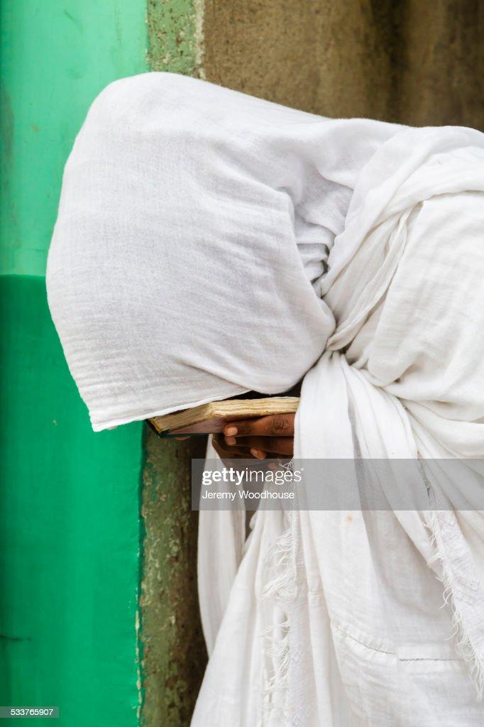 Close up of pilgrim praying in white robes : Foto stock