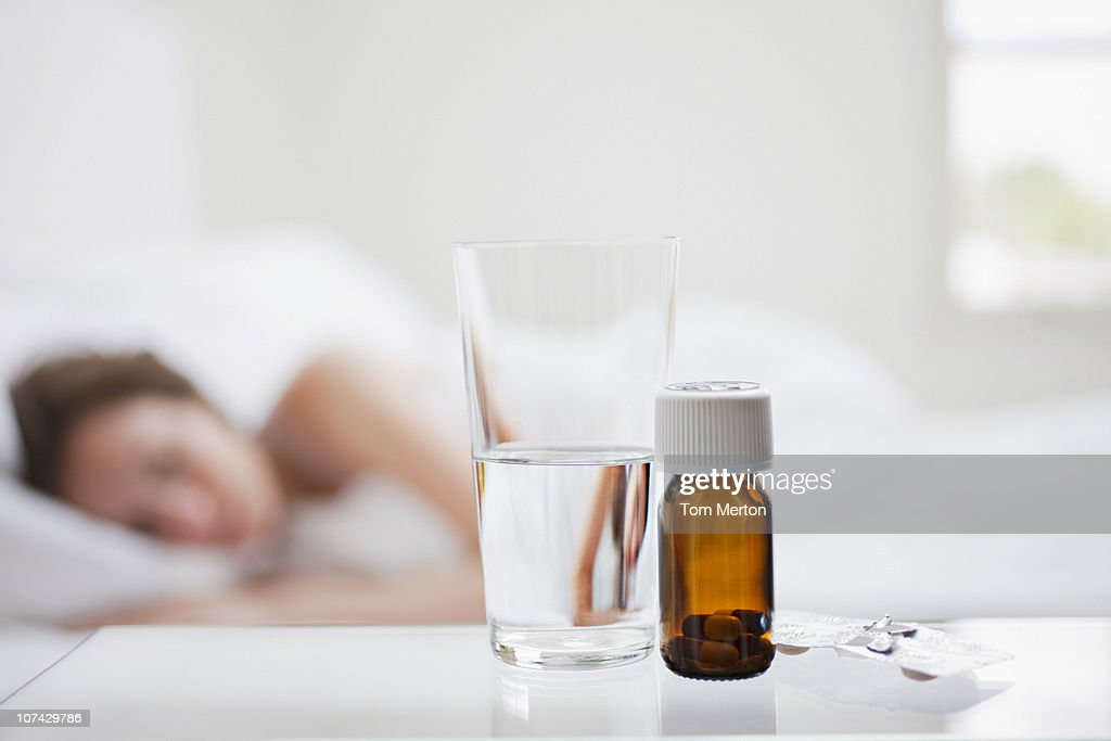 Close up of pill bottle with sick woman in background : Stock Photo