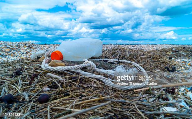 close up of plastic bottle and rope mooring bouy weathered on beach save our oceans pollution - pollution stock pictures, royalty-free photos & images