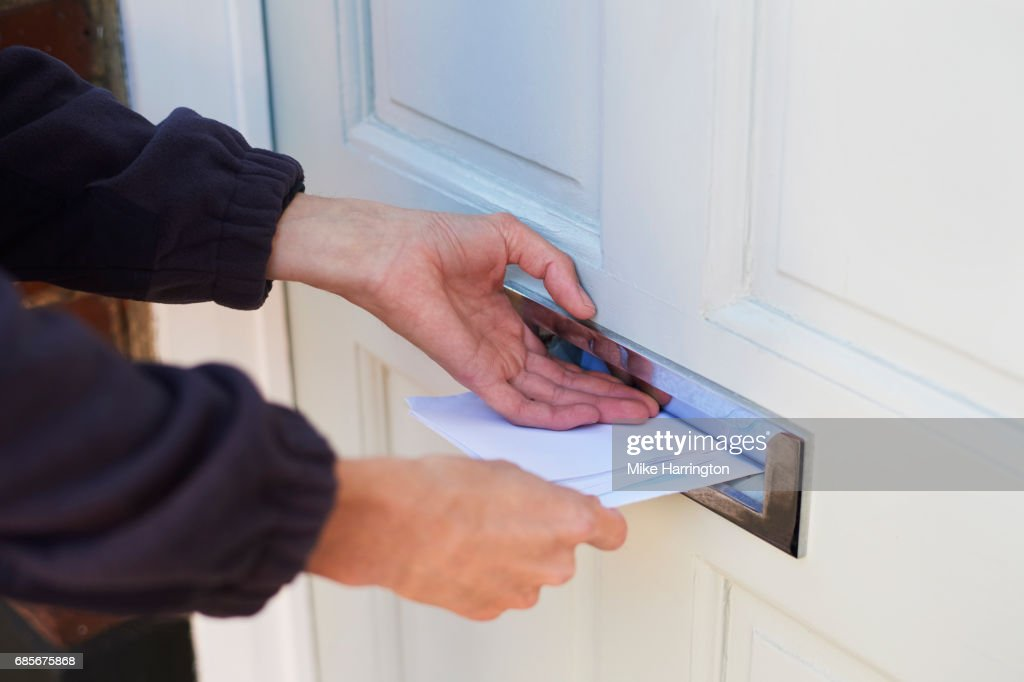 Close up of postman delivering letters : Stock Photo