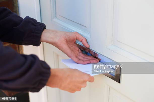 close up of postman delivering letters - bericht stockfoto's en -beelden