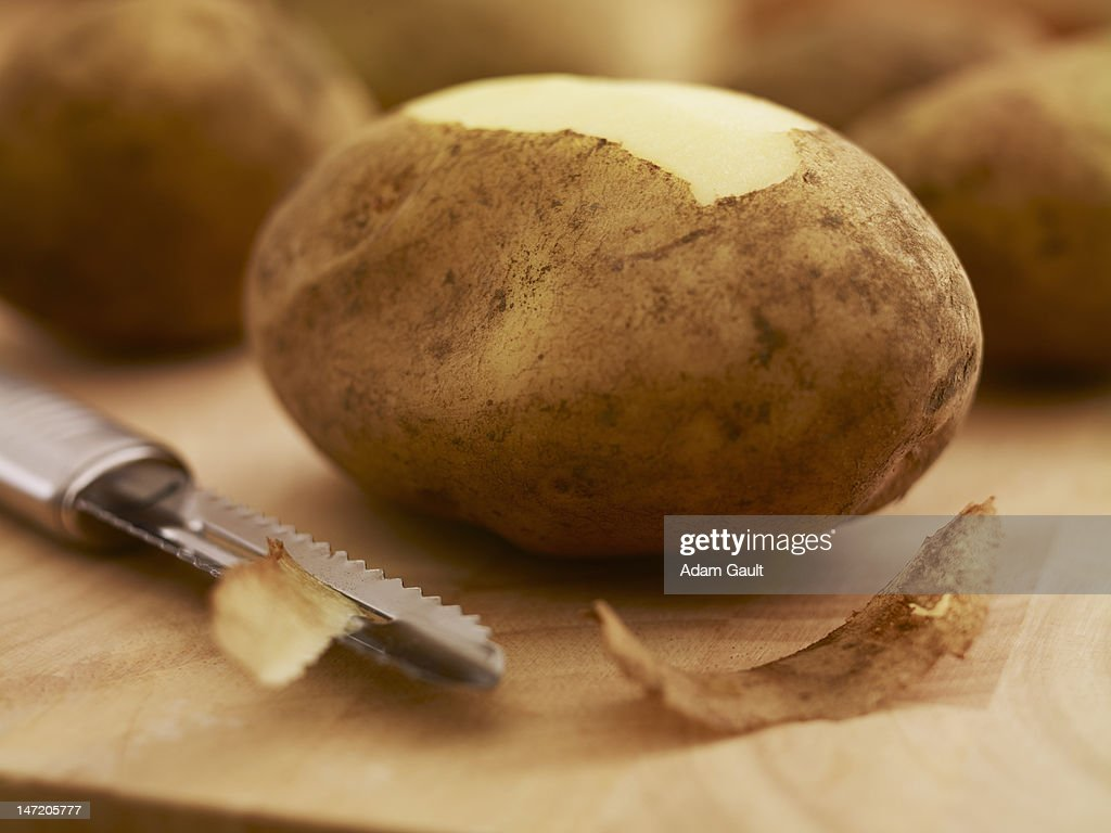 Close up of potato and peeler on cutting board : Stock Photo