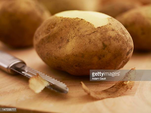 close up of potato and peeler on cutting board - dunschiller stockfoto's en -beelden