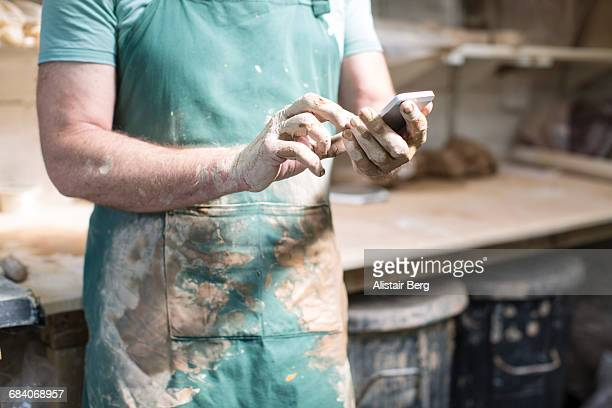 close up of potter looking at smart phone - mid section stock photos and pictures