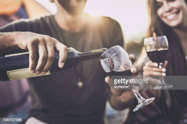 close up of pouring red wine into a glass outdoors. - drink stock pictures, royalty-free photos & images