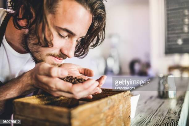 eine nahaufnahme von professionellen barista in einem café, kaffeebohnen riechen. - etwas herstellen stock-fotos und bilder