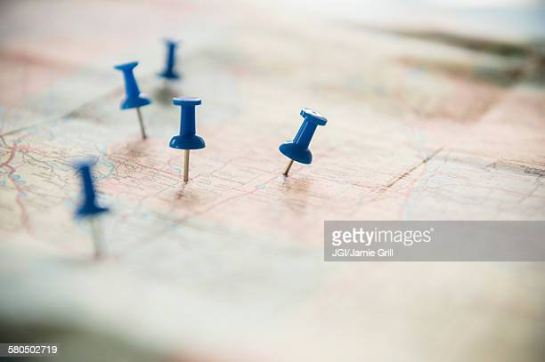 close up of pushpins on roadmap route - cartography stock photos and pictures