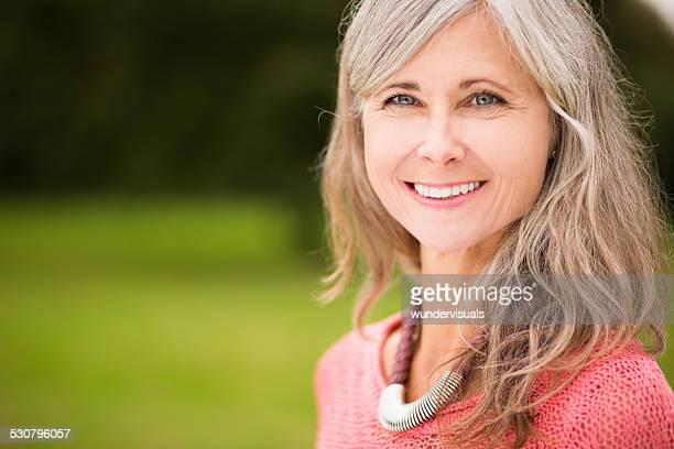 Close Up Of Radiant Mature Woman Standing In Park