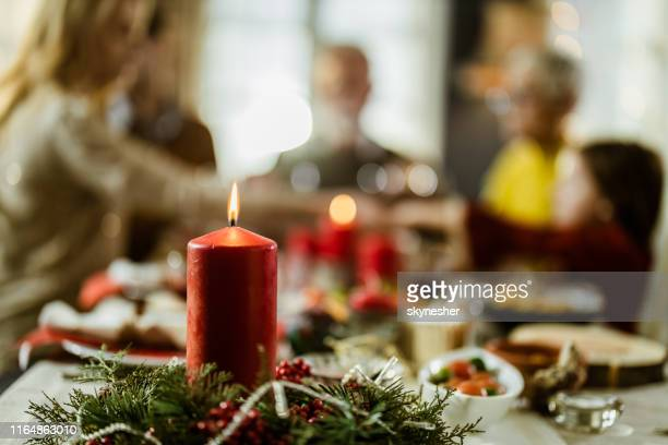 close up of red christmas candle on dining table. - avvento foto e immagini stock
