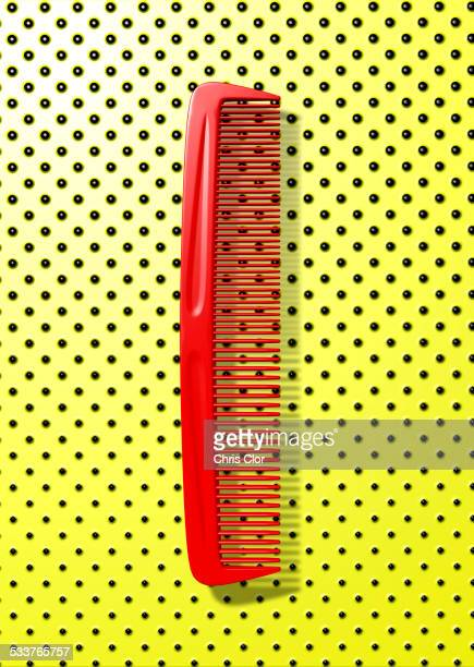 Close up of red comb on polka dot background