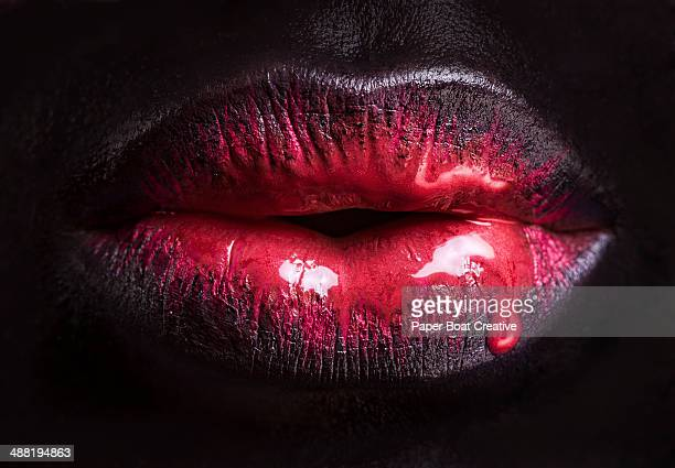 close up of red paint dripping over black lips - menselijke lippen stockfoto's en -beelden