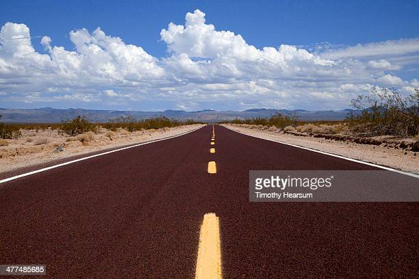 close up of red paved highway through desert - timothy hearsum stock pictures, royalty-free photos & images