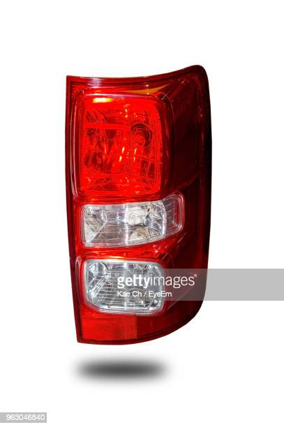 close up of red tail light against white background - vehicle light stock photos and pictures