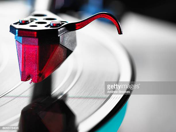 close up of red turntable stylus playing a vinyl record - saffier stockfoto's en -beelden