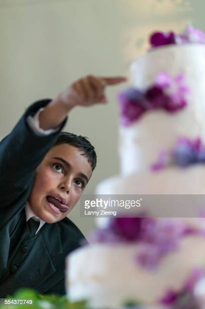 Close up of ring bearer sneaking frosting from wedding cake