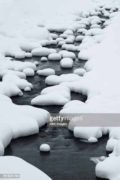 Close up of riverbed with snow-covered rocks in winter.