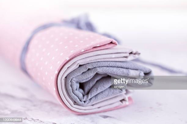 close up of rolled pale colored fabrics on marble table - ribbon sewing item stock pictures, royalty-free photos & images