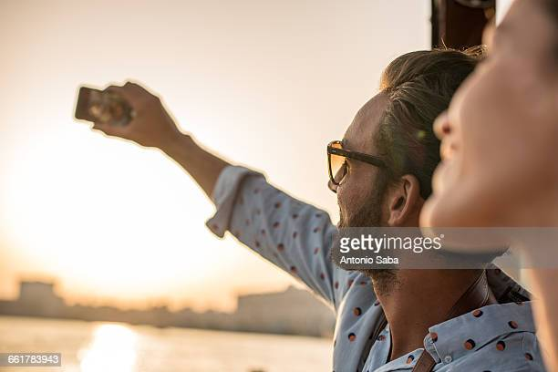 Close up of romantic couple taking smartphone selfie at Dubai marina, United Arab Emirates