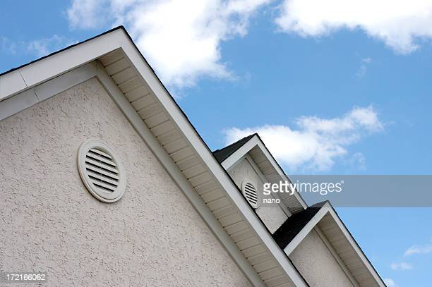 close up of roof peaks against blue sky - eaves stock photos and pictures