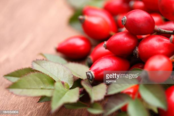Close up of rose hip berries and leaves on wooden table