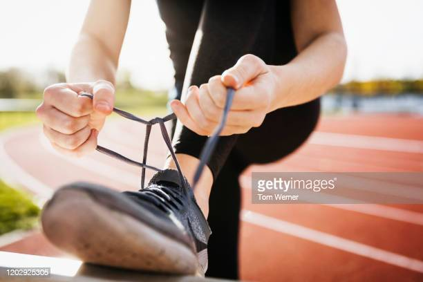 close up of runner tying shoelaces - tying shoelace stock pictures, royalty-free photos & images