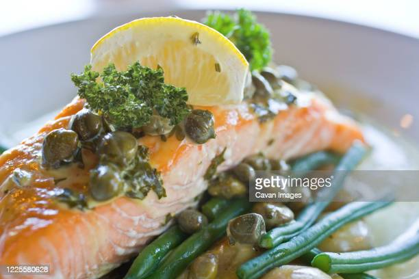 close up of salmon with capers and lemon - ラニーメイド ストックフォトと画像