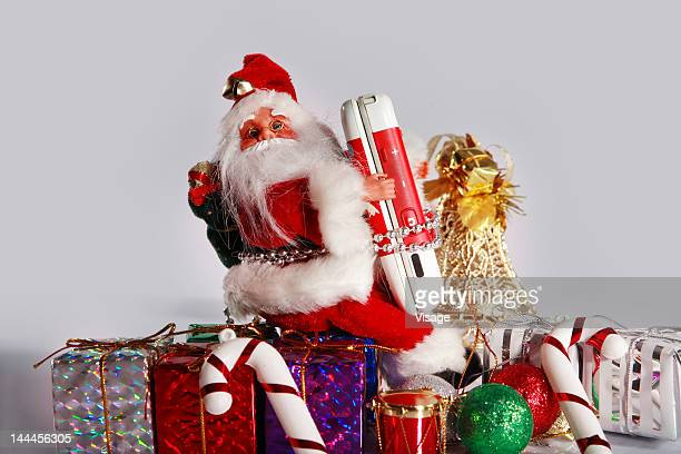 close up of santa claus doll with gifts and cell phone - candy dolls fotografías e imágenes de stock