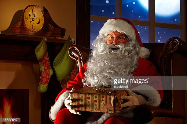 close up of santa holding a christmas gift - santa close up stock pictures, royalty-free photos & images