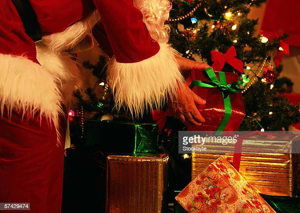 close up of Santa's hands putting presents under a Christmas tree