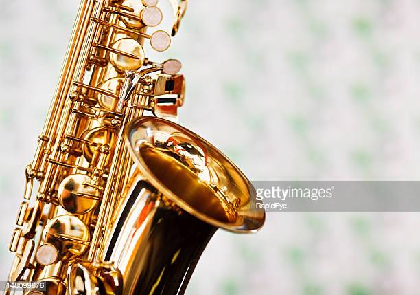 Close up of saxophone against faded green and white fabric