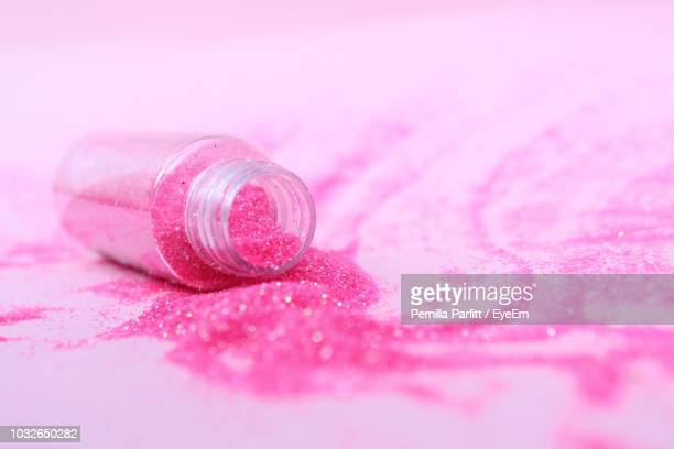 close up of scattered pink glitter with bottle on table - pink sparkles stock pictures, royalty-free photos & images