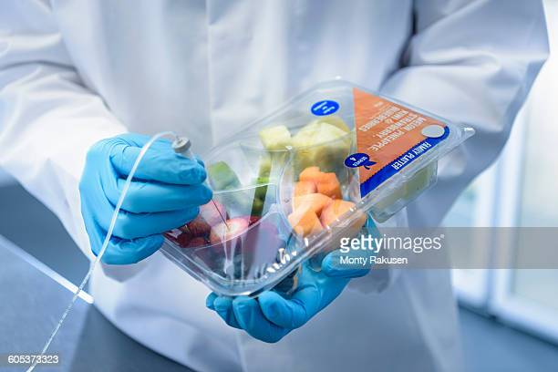 Close up of scientist inspecting food for freshness in laboratory in food packaging printing factory