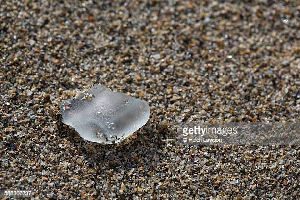 Close up of sea glass on sandy beach