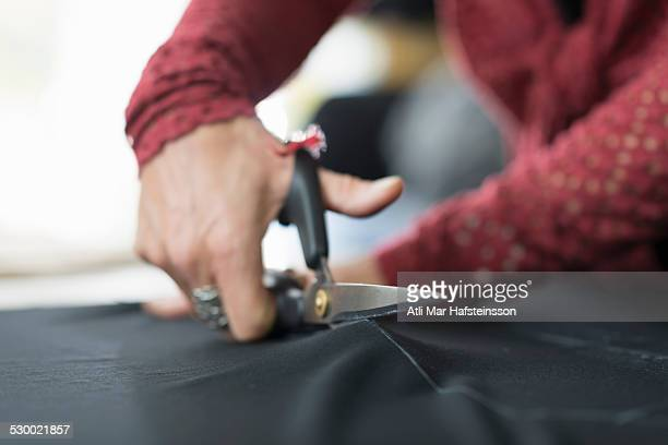 Close up of seamstress hands using scissors to cut textile at work table