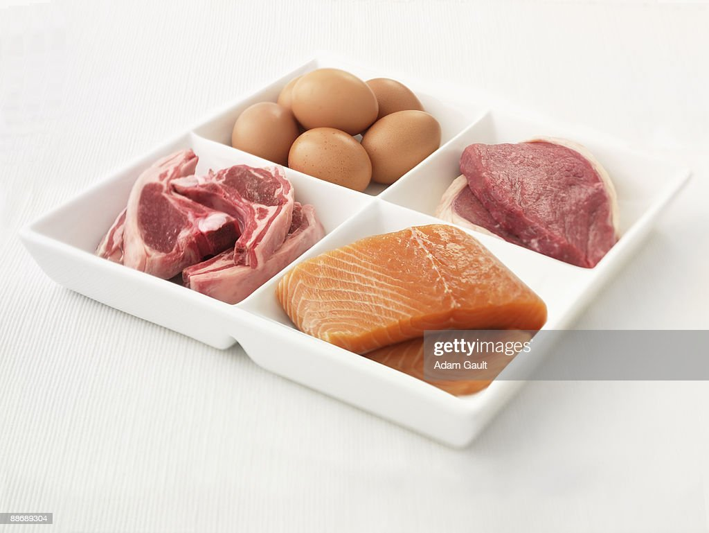 Close up of sectioned plate with eggs, pork, salmon and steak : Stock Photo
