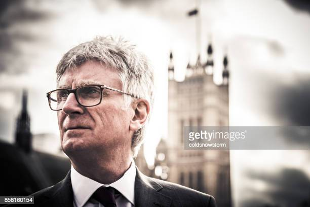 close up of senior caucasian businessman outside houses of parliament, london, uk - politician stock pictures, royalty-free photos & images