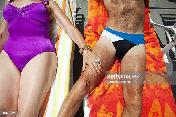 close up of senior couple sunbathing - old man in speedo stock photos and pictures