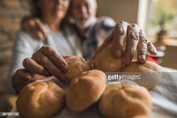 Close up of senior couple taking fresh buns for breakfast.