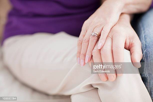close up of senior couple touching hands - man touching womans leg stock photos and pictures