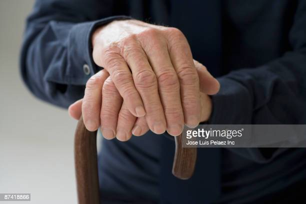 close up of senior hispanic manâ¿s hands on cane - vulnerability stock pictures, royalty-free photos & images