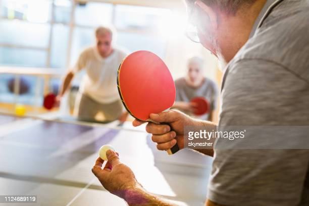 close up of senior man playing table tennis in health club. - table tennis stock pictures, royalty-free photos & images