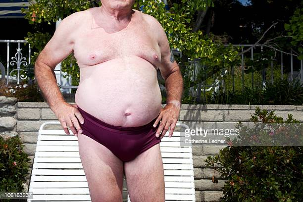 close up of senior man's stomach - man wearing speedo stock photos and pictures