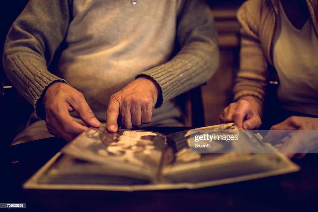 Close up of senior people remembering their old photos. : Stock Photo