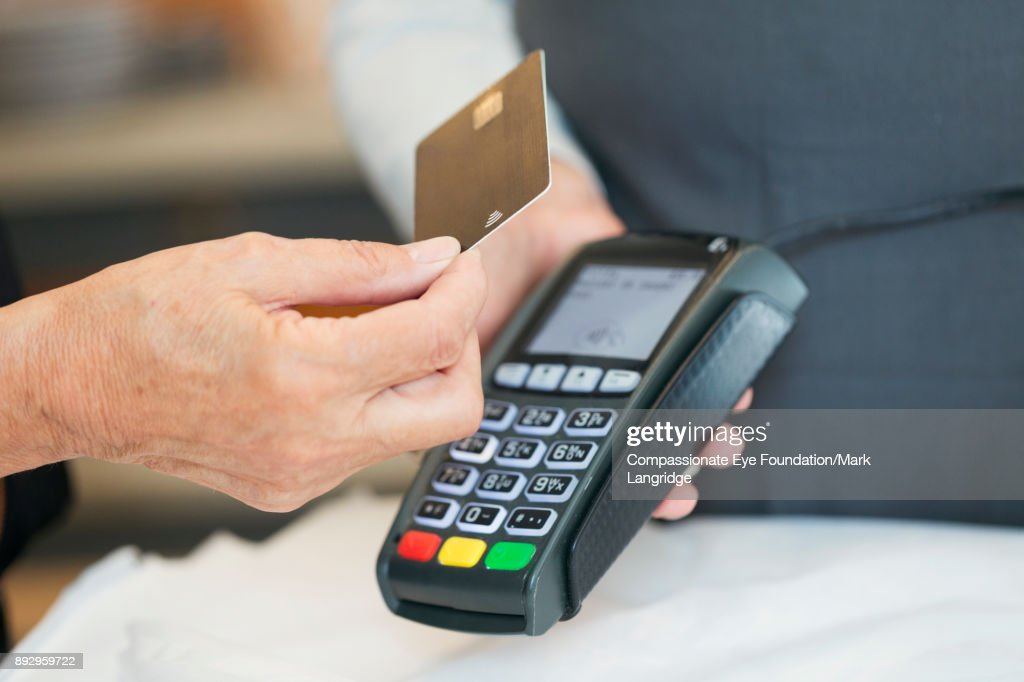 Close up of senior woman using contactless payment in shop : Stock Photo