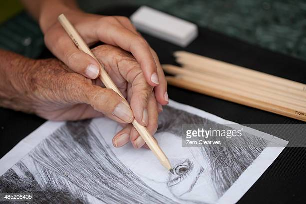 Close up of senior woman's hand doing a pencil drawing