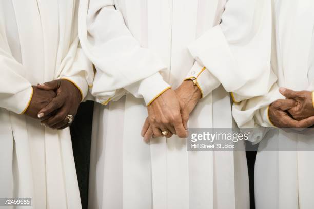 close up of senior women in choir gowns with hands clasped - ceremonial robe stock pictures, royalty-free photos & images